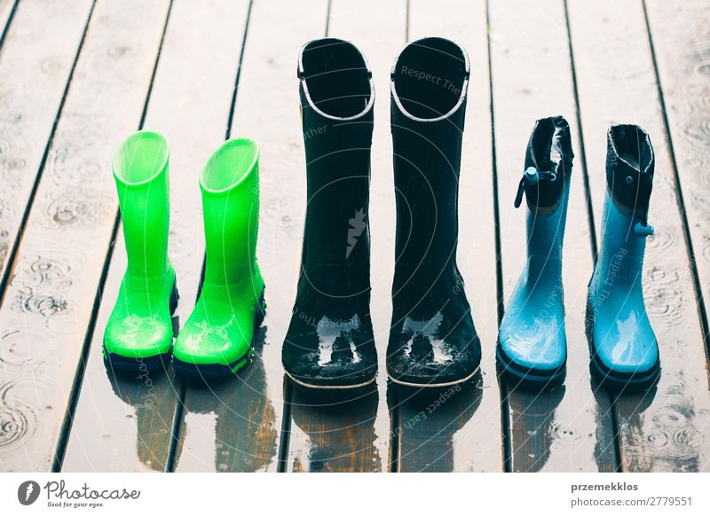 Row of wellies standing on a wooden porch while raining Joy Summer Child Human being Woman Adults Man Weather Rain Coat Footwear Boots Rubber boots Small Wet