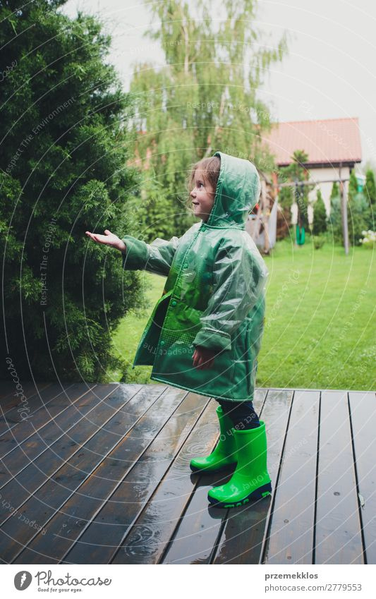 Little girl standing on rain wearing green raincoat Lifestyle Joy Happy Summer Child Human being Woman Adults Infancy Weather Rain Coat Boots Rubber boots