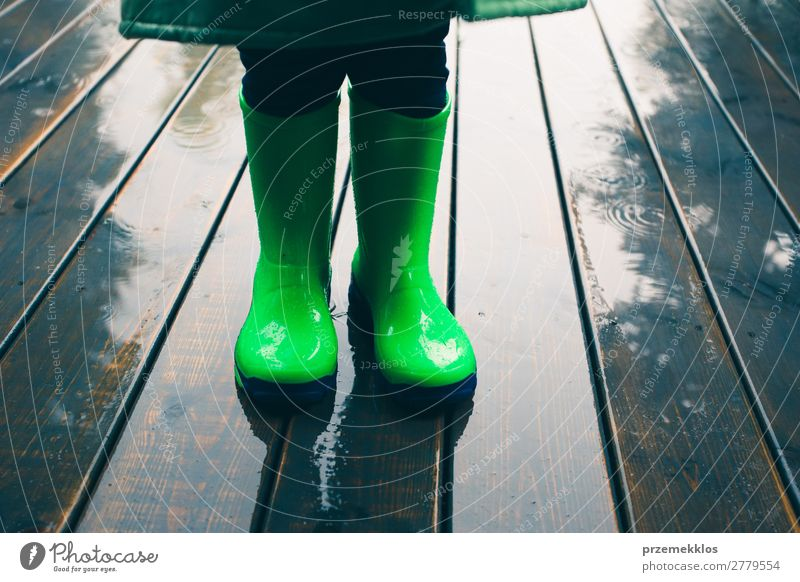 Kid standing on a porch wearing green wellies and raincoat Joy Summer Child Human being Boy (child) Weather Rain Coat Footwear Boots Rubber boots Small Wet Cute
