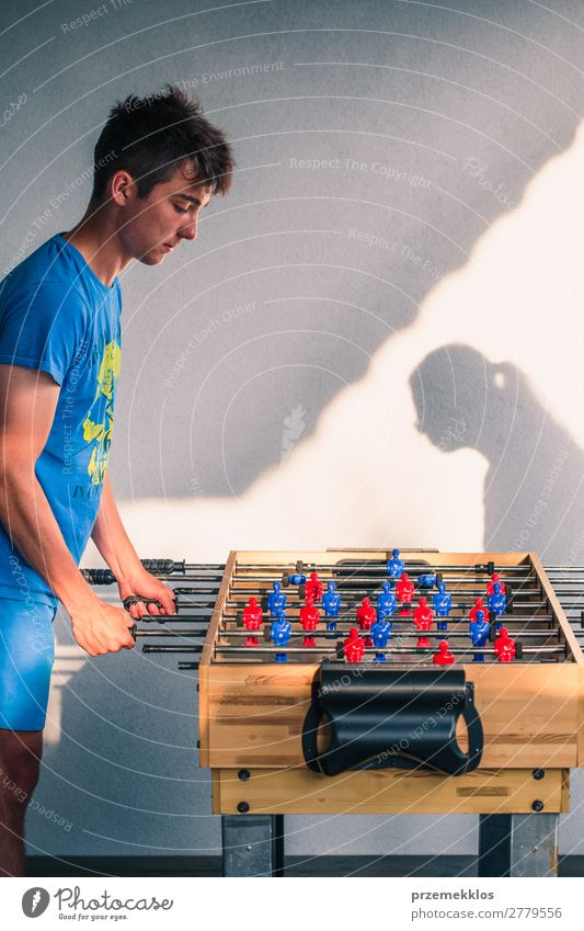 Young teenager boy playing table football with another player. Lifestyle Joy Relaxation Leisure and hobbies Playing Summer Table Sports Soccer Boy (child) Man