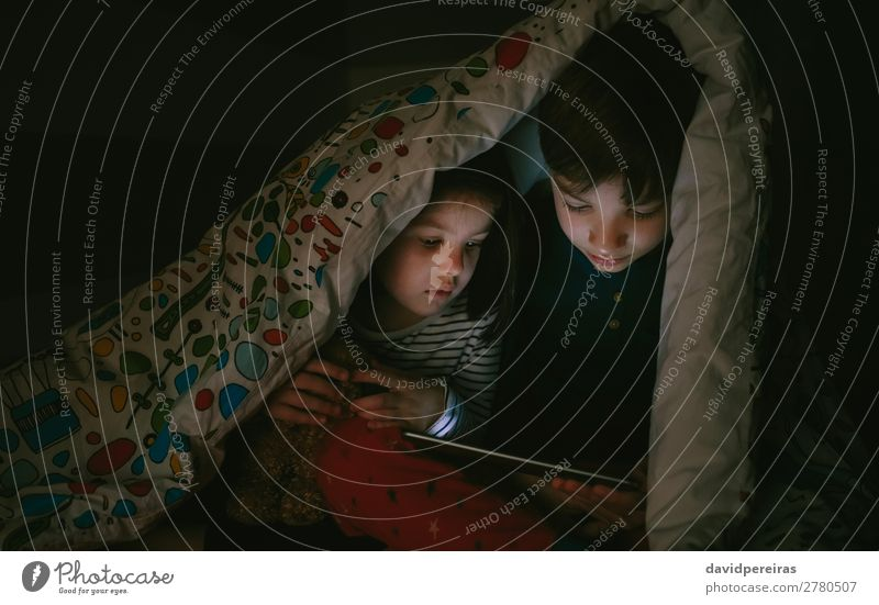 Kids sitting on the bed looking tablet in the dark Lifestyle Face Calm Playing Bedroom Child Technology Internet Human being Boy (child) Woman Adults Man Sister