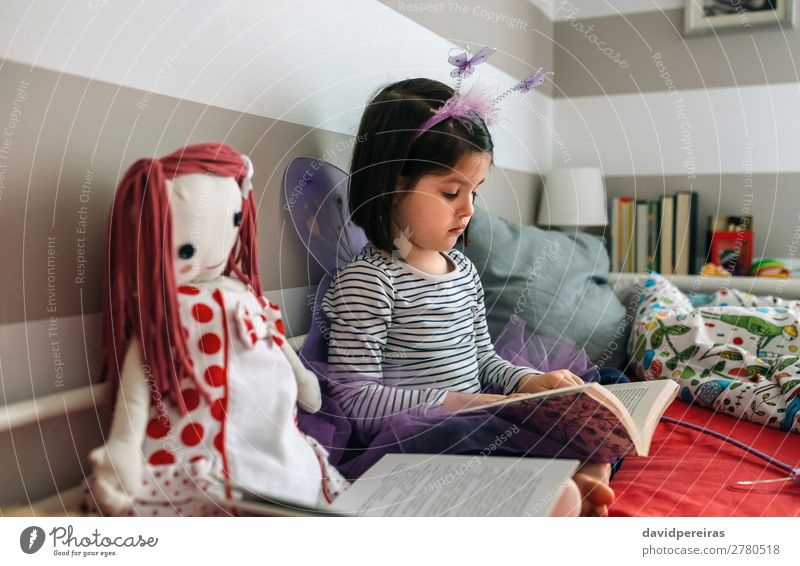 Girl disguised as a butterfly reading with her doll Lifestyle Beautiful Playing Reading Lamp Bedroom Child Human being Woman Adults Friendship Infancy Book