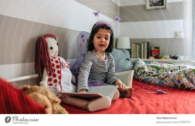 Girl disguised as a butterfly teaching her doll to read Lifestyle Beautiful Playing Reading Lamp Bedroom Child Human being Woman Adults Friendship Infancy Book