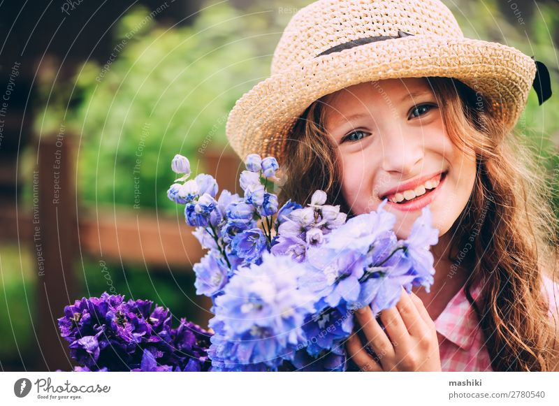 romantic portrait of happy child girl picking bouquet of beautiful blue delphinium flowers from summer garden plant blossom kid play smile funny gardener helper