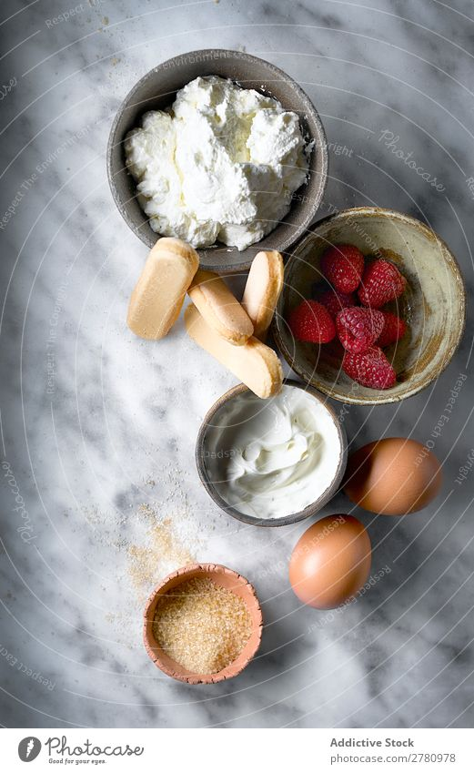 Top view of cake ingredients on table Ingredients Cake Fresh products biscuits Raspberry Cream Conceptual design Egg Sugar composition Marble Arrangement Food