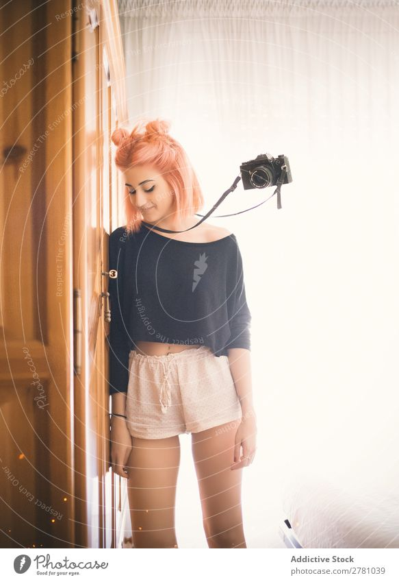 Film camera flying beside young pink-haired woman Camera Woman Portrait photograph Flying levitate Vintage pink hair Attractive beauitful Strange