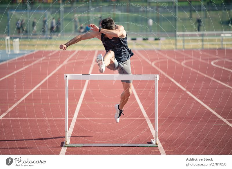 Man jumping over hurdle Running Hurdle Racecourse Athlete Track Determination Competition competitive Runner Speed Field hurdling compete Exterior shot sprint