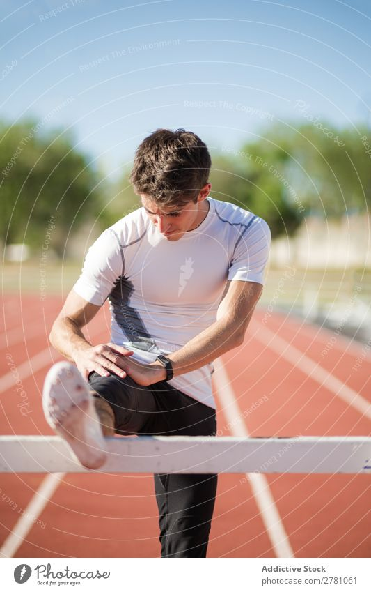 Young sportsman stretching legs Man Stretching Stadium Posture Flexible Fitness Practice Athlete Sports Muscular Health care Adults Sprinter Athletic