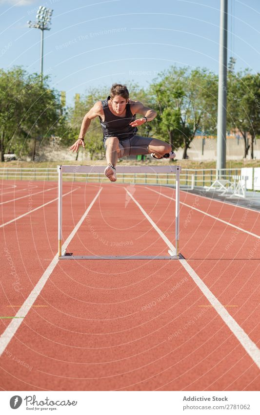 Sportsman jumping over a hurdle sportsman Posture Stadium Stand Fitness Athlete Racecourse Practice Plank Man Muscular Health care Adults Sprinter Athletic