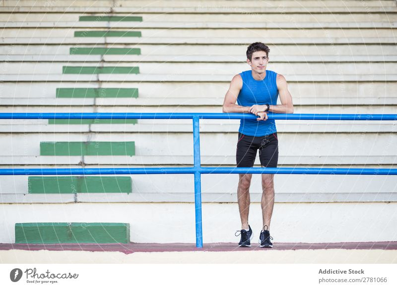 Sportsman posing on stadium Man Stadium Athletic Posture Rest sportsman Fitness Contentment Practice Lean Athlete Muscular Relaxation Adults Sprinter Fence