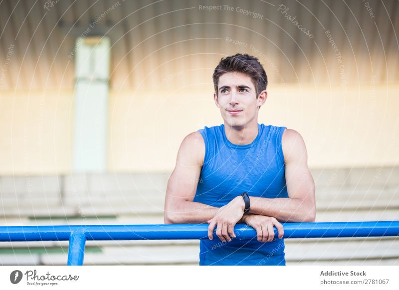 Young man in sportswear leaning on metal fence and posing on sta Man Stadium Athletic Posture Rest sportsman Sports Fitness Contentment Practice Lean Athlete