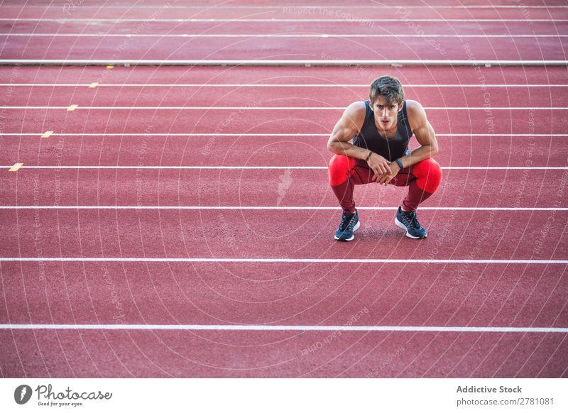 Sportsman sitting on race track Man Racecourse Rest Posture sportsman Squat Fitness Practice Athlete Sit Muscular Relaxation Adults Stadium Sprinter Break