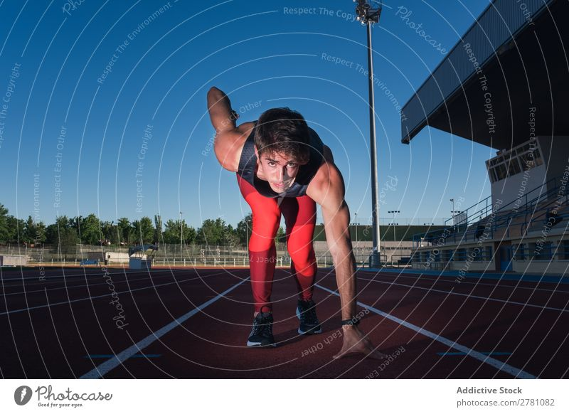 Young male sprinter ready to run Man crouch start Racecourse Concentrate Stadium Athletic Fitness Summer Sprinter Athlete Sports Adults Sportswear Track Runner