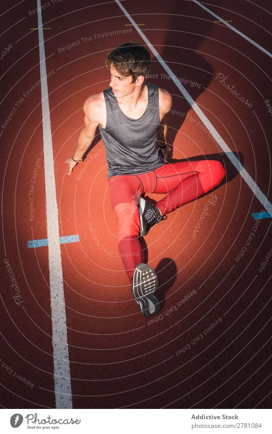 Sportsman in light on race track Man Racecourse Posture sportsman Fitness Practice Athlete Muscular Relaxation Adults Stadium Sportswear Athletic