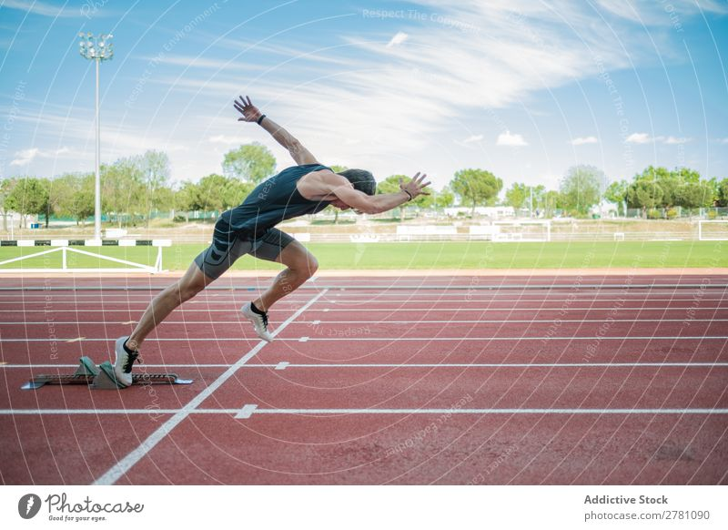 Side view of male sprinter sportsman Runner Racecourse crouch start Sprinter Stadium Success Sports Fitness Practice Athlete Muscular Adults Sportswear Athletic