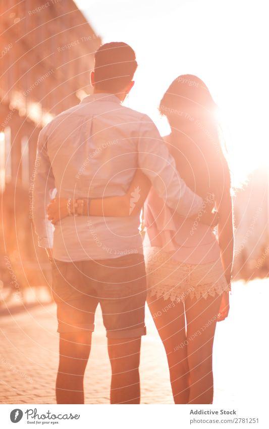 Unrecognizable hugging couple in sunny street Couple Embrace Street Rear view Sunlight Bright Walking Stand Observe Vertical Stern Blur Sunbeam Brunette