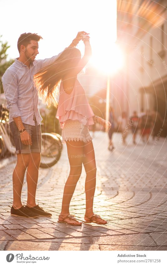 Girlfriend with flying hair dancing in the street holding her boyfriend's hand Couple Dance Street Romance Sunlight Bright Hold Arm