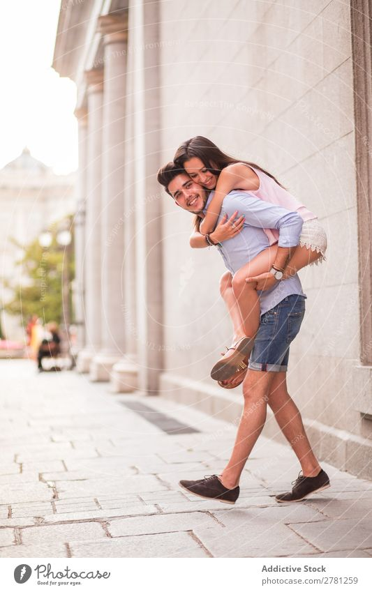 Smiling couple in the street. Couple piggy back Joy Hold Emotions Happy Cheerful Carrying Vertical Day Blur Building Stand Profile Embrace Looking away