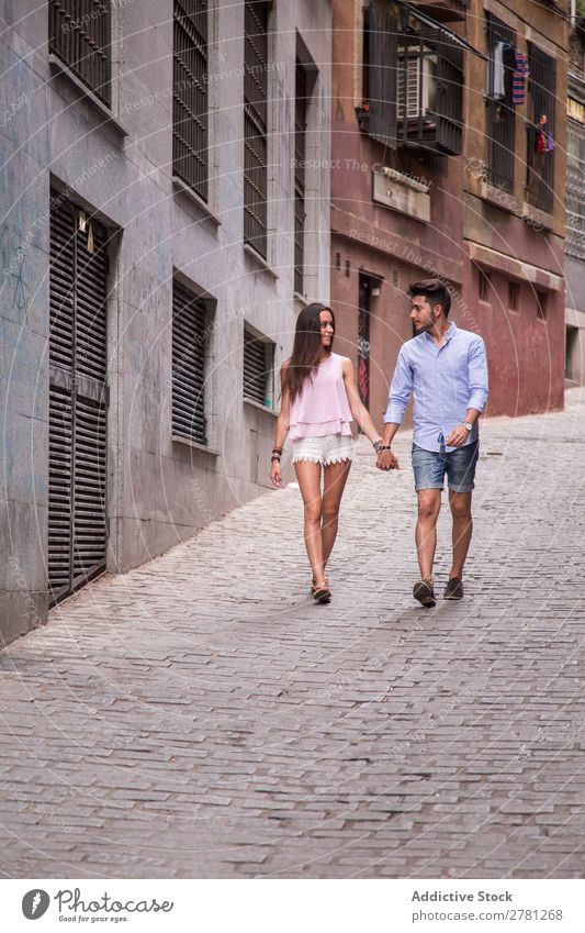 Young lovers walking on street Couple Happy Hold Hand Walking Woman Face to face Style