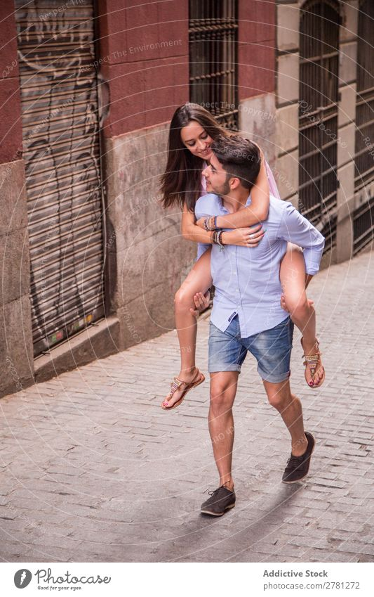 Stylish young guy carries pretty girl on back Man Carrying Back Girl Couple Woman Style boyfriend girlfriend Ride Hold City Human being Cheerful Hip & trendy
