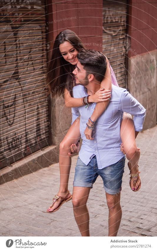 Smiling girl rides on back of boyfriend Couple Ride Girl Back Woman Man girlfriend Hold City Human being Cheerful Hip & trendy piggyback Youth (Young adults)