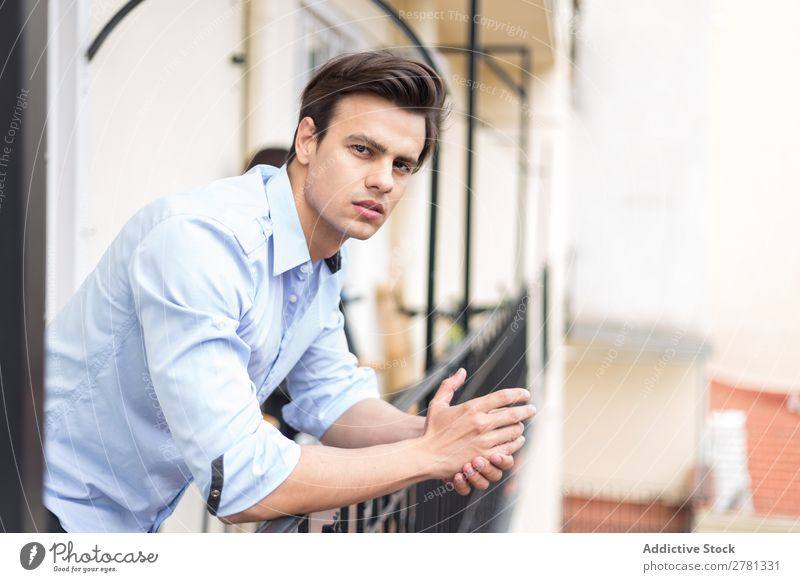 Young serious man in blue shirt posing Man Earnest Stand Balcony Portrait photograph Gesture Considerate Pensive Posture Human being 1 Youth (Young adults)