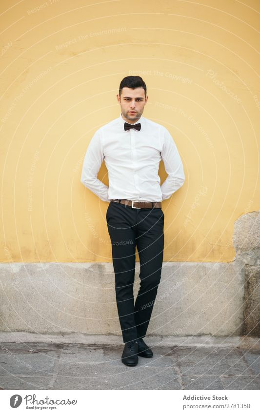 Welldressed Businessman Leaning On Yellow Wall 20s Adults Architecture Attitude Back Behind Bow tie Businesspeople Businessperson Caucasian Self-confident