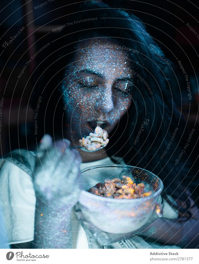 Woman with glitters on face eating cereal Youth (Young adults) pretty Colour Painting (action, artwork) Eating Cereal Food Breakfast Gray Fluorescent Illuminate