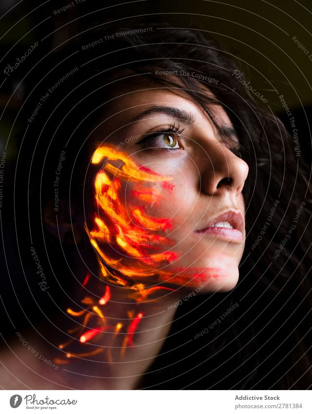 Woman with luminous paint on face Youth (Young adults) pretty Colour Painting (action, artwork) Orange Fire Passion Looking away Fluorescent Illuminate Art Neon