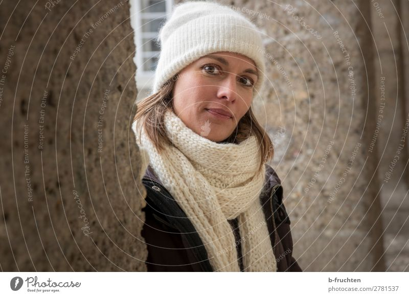 Portrait of woman with scarf and cap Relaxation Woman Adults Head 1 Human being Wall (barrier) Wall (building) Coat Scarf Cap Observe Looking Stand Friendliness