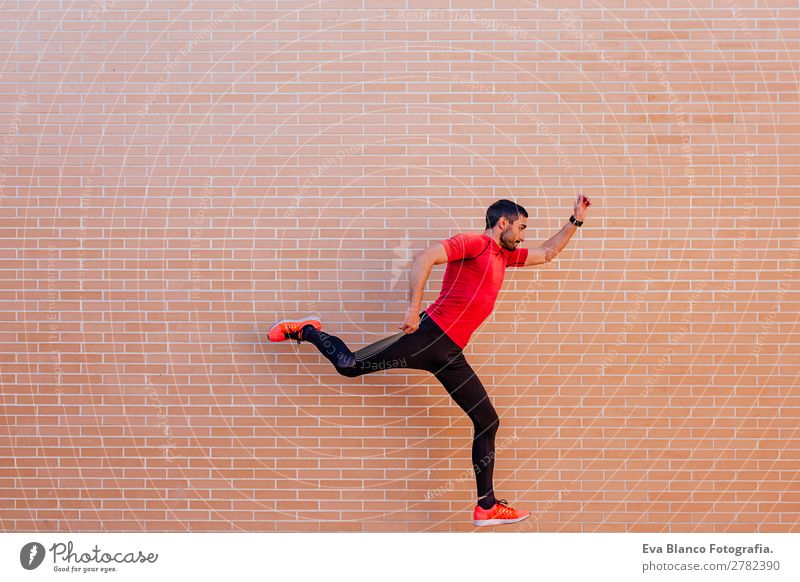 young athlete man jumping over brick background Lifestyle Leisure and hobbies Sports Track and Field Jogging Stadium Human being Masculine Man Adults