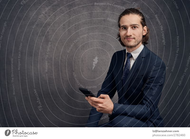 Handsome young man with long hair, wearing stylish suit and blue tie Roll Style Face Reading Success Business PDA Technology Man Adults Suit Tie Smiling Sit