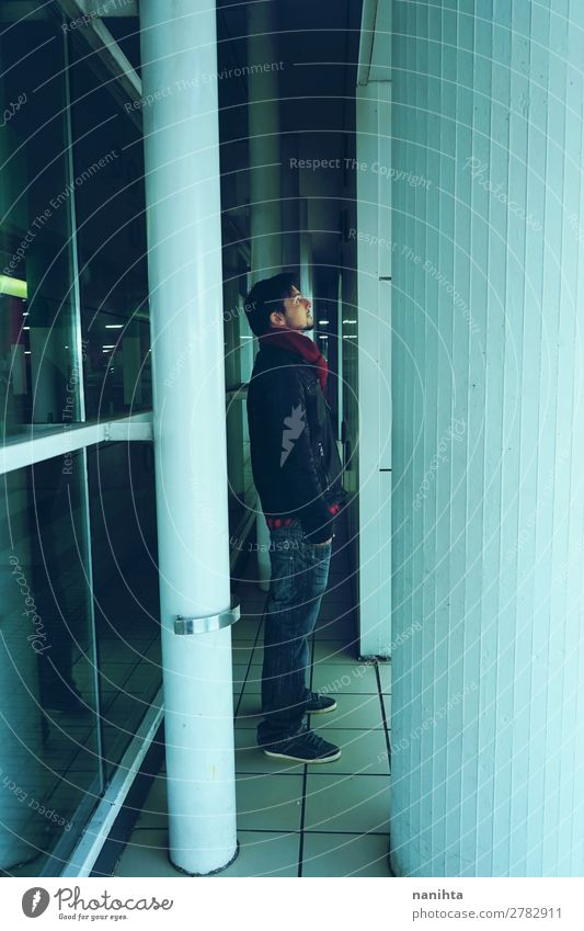 Young man alone in a bus station at night Lifestyle Winter Mirror Human being Masculine Youth (Young adults) Man Adults Sadness Town Blue Hope Loneliness