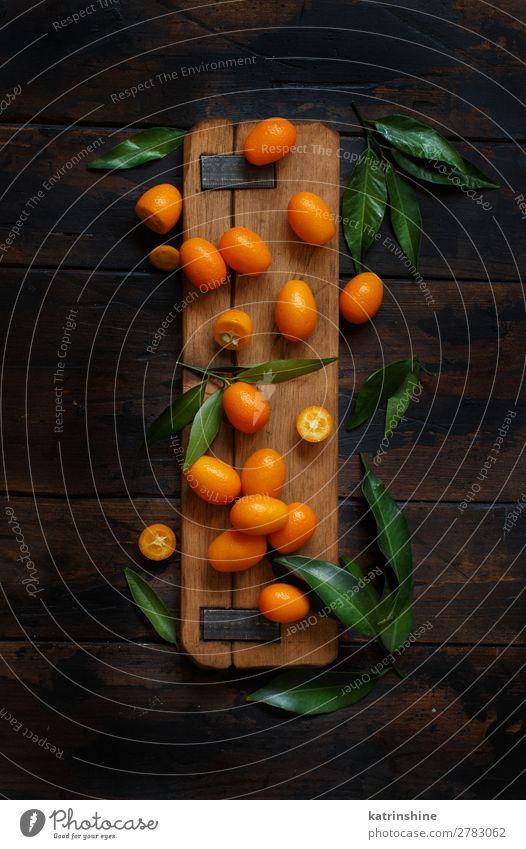 Kumquat fruits on a dark wooden background Fruit Dessert Nutrition Vegetarian diet Diet Exotic Group Leaf Dark Fresh Natural Above Juicy Brown Yellow Colour