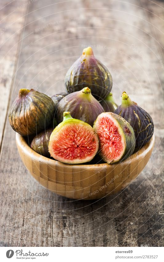 A few figs in a bowl on an old wooden background Fig Fruit Food Healthy Eating Food photograph Exotic Sweet Raw Red Fresh Tropical Slice Wood Group Half Natural