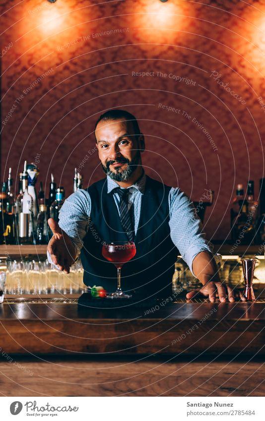 Barman is making cocktail at night club. Cocktail shaker barman bartender Waiter Man Portrait photograph portraiture Stir mixologist adding Alcoholic drinks