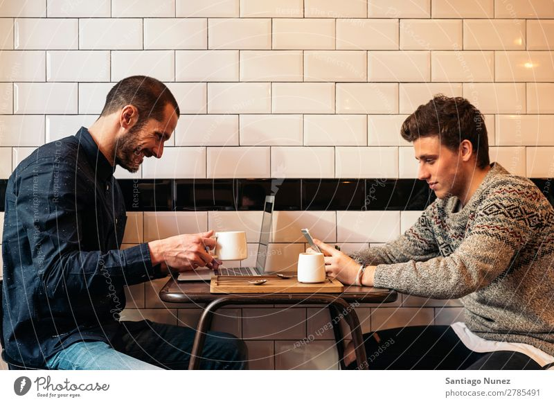 Friends using mobile and laptop. Man Coffee Friendship Youth (Young adults) Teamwork Group Human being Lifestyle PDA Cellphone Mobile Communication Text