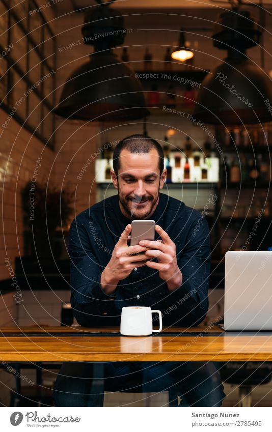 Businessman using his mobile in the Coffee Shop. Man Friendliness Portrait photograph Youth (Young adults) Human being Lifestyle Communication PDA Cellphone