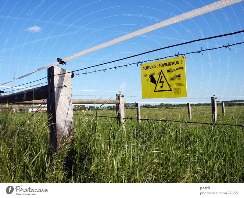 Watch your step! Power fence! Meadow Warning sign Electricity Green Clouds Vapor trail Barbed wire Fence. electric fence Signs and labeling Warning label
