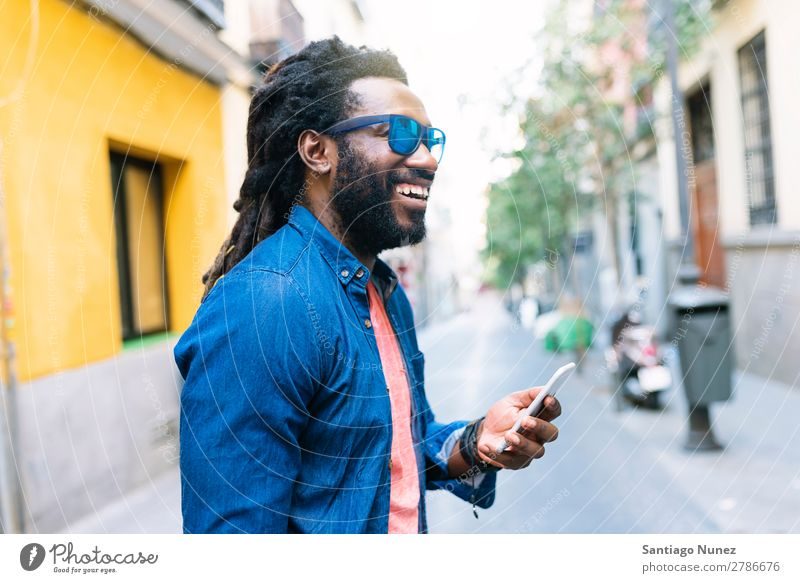 African Young Man Using Mobile In The Street Lifestyle Listening Black American Town Portrait photograph Telephone PDA Solar cell Communication texting Email