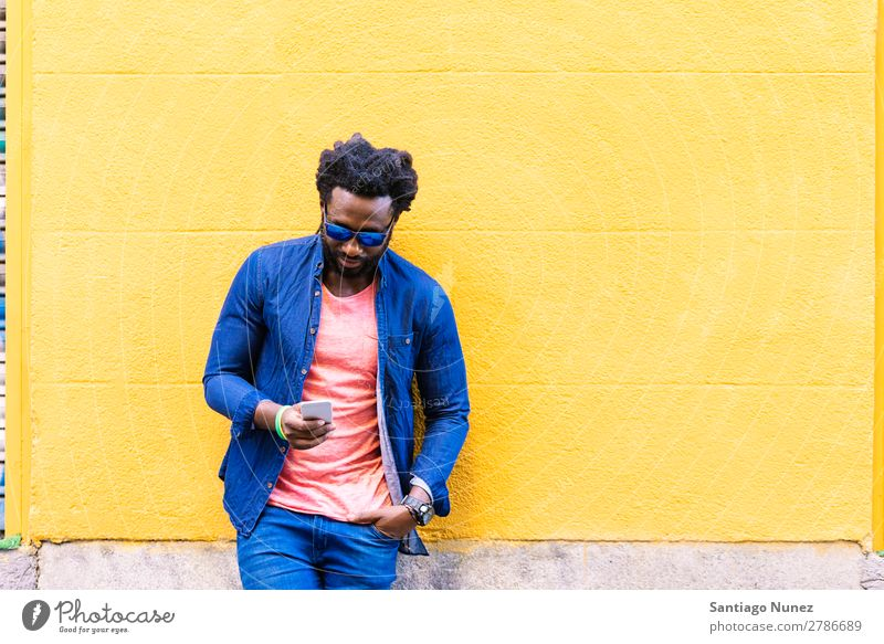 African Young Man Using Mobile In The Street. Lifestyle Listening Black American Town Portrait photograph Telephone PDA Solar cell Communication texting Email