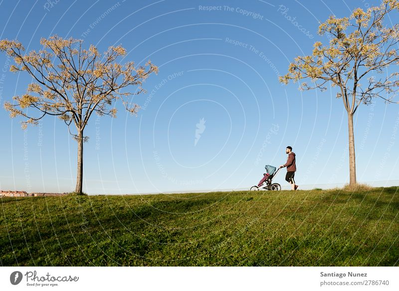 Father and son walking in the park. stroller Jogging Running Walking Buggy (Motorbike) Family & Relations Baby Child Youth (Young adults) Daughter Son