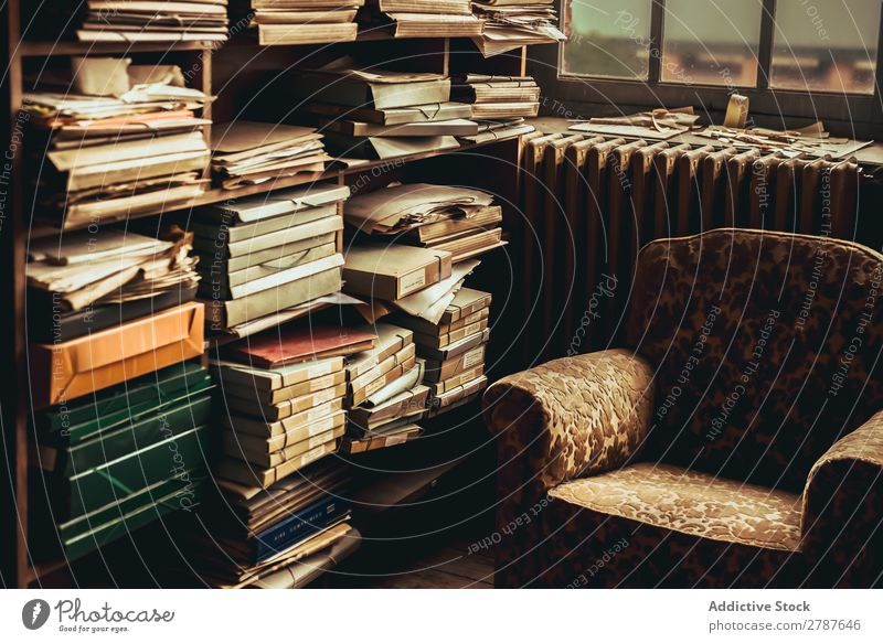 Old armchair near shelves with heap of papers Armchair shelf Heap Paper composition archive Vintage Document Room Accumulation Employees & Colleagues type