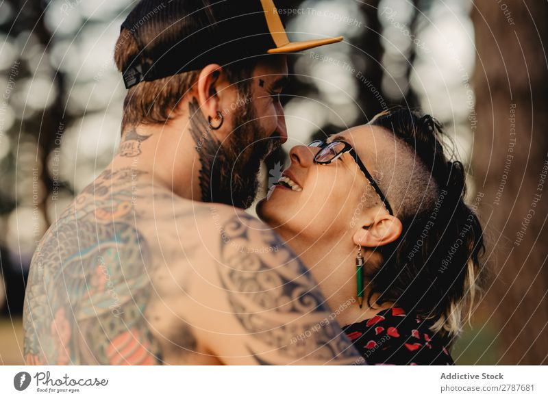 Young guy in tattoos hugging lady in forest Couple Tattoo Embrace Forest snapback Park Lady shirtless Guy Youth (Young adults) Hipster embracing Man Woman
