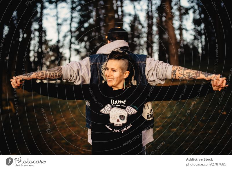 Young guy and happy lady standing back to back in forest Couple Tattoo Forest snapback Park Happy holding hands Lady Guy Youth (Young adults) Hipster Smiling