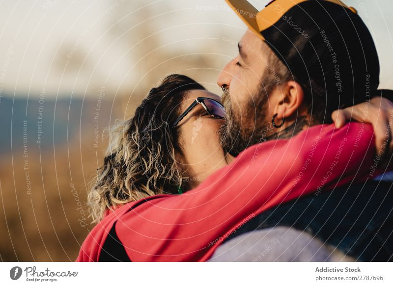 Young lady biting guy in tattoos Couple Tattoo Neck Eyeglasses Earring snapback Lady Guy Youth (Young adults) Hipster Man Woman embracing romantic Embrace Art