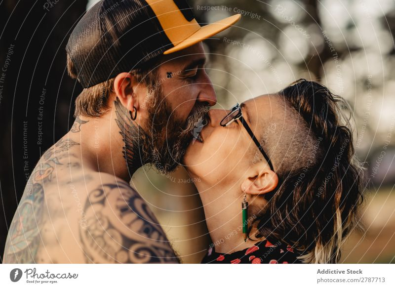 Happy couple hugging and kissing near tree in park Couple Embrace Park Tree embracing Back Wood Forest Youth (Young adults) Cheerful bearded Man Woman Joy