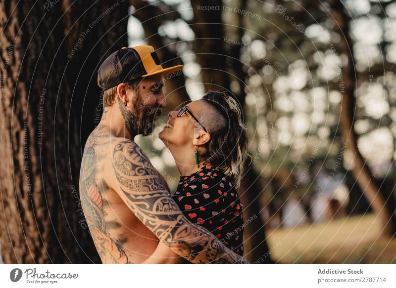 Happy couple hugging near tree in park Couple Embrace Park Tree embracing Back Wood Forest Youth (Young adults) Cheerful bearded Man Woman Joy Hipster Walking