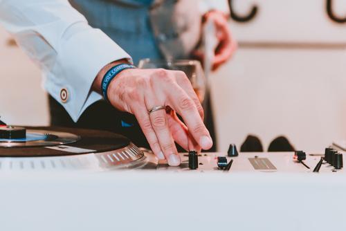 Man using music equalizer near glass of drink Music Glass Drinking audio Sound Disc jockey Equipment Shirt Hand Beverage Professional Technology Producer