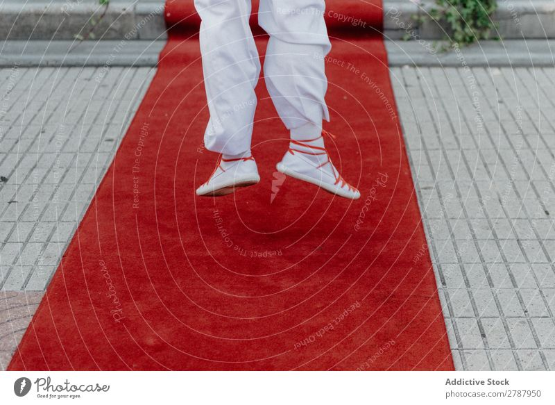Person in white cloth and gym shoes jumping on red carpet Red carpet Human being Suit Cloth White Jump Legs Street